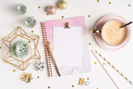 Desktop blank note pad. Flat lay of white working table background with cup of coffee and Christmas decoration. Top view balls, fir tree, paper clips, mock up greeting card, craft Notebook and pen. Banque d'images