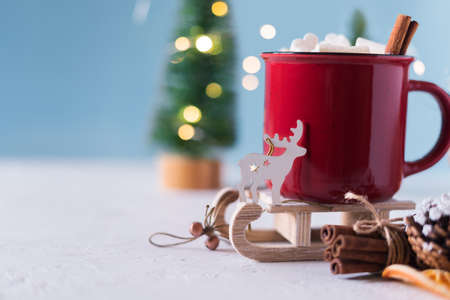 Winter hot drink, cacao with marshmallows and cinnamon or spicy hot chocolate in red cup. Merry Christmas. Festive vintage background. Copy space for text.