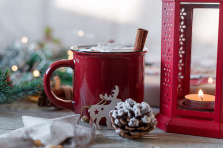 Winter hot drink, cacao with marshmallows and cinnamon or spicy hot chocolate in red cup and Christmas garland. Festive vintage background. Banque d'images