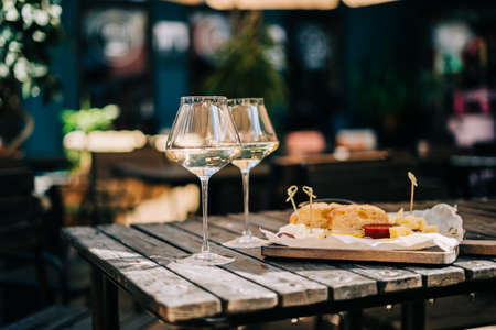 A wooden table in a restaurant with a cheese plate, grape, honey bread and white wine. Wine glasses and cheese served for a party in a blurred bar or a restaurant on patio at a sunny summer day.