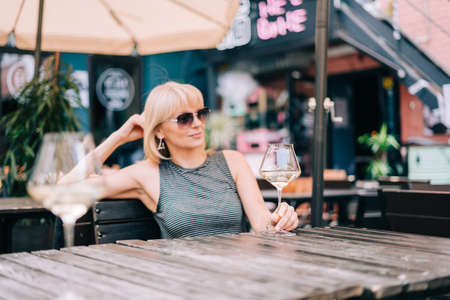 Smiling mature woman in eyeglasses sitting on couch in bar outdoors with wine glasses and blurry restaurant background, drinking white wine, eating cheese. Summer sunny day on patio. People lifestyle