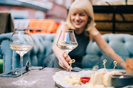 Happy and laughing adult mature woman sitting in bar outdoors with wine glasses and blurry restaurant background scene, drinking white wine and eating cheese. Summer sunny day on patio.