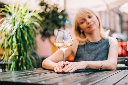 Happy adult mature woman sitting at table in bar outdoors with wine glasses and blurry restaurant background scene, drinking white wine. Summer sunny day on patio with plants. People lifestyle
