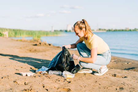 Young female volunteer satisfied with picking up trash, a plastic bottles and coffee cups, clean up beach with a sea. Woman collecting garbage. Environmental ecology pollution concept. Earth Day.
