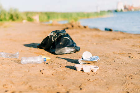 Trash on the beach. Used garbage, plastic wasted water bottle, coffee cup, highlighting the worldwide crisis of plastic pollution. Environment ecology concept. Banque d'images