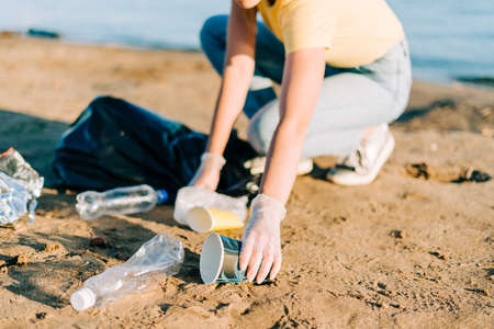 Young female volunteer hand satisfied with picking up trash, a plastic bottles and coffee cups, clean up beach with a sea. Woman collecting garbage. Environmental ecology pollution concept. Earth Day.