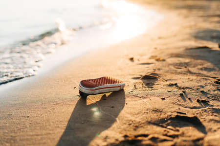 Used old shoe washed up on the shore of a beach, highlighting the worldwide crisis of garbage, plastic pollution. Environment ecology concept Banque d'images