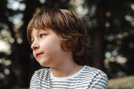 Portrait of cute boy in the forest thoughtfully looking afar. Blue eyed school kid day dreaming in the park. Relaxing outdoors.