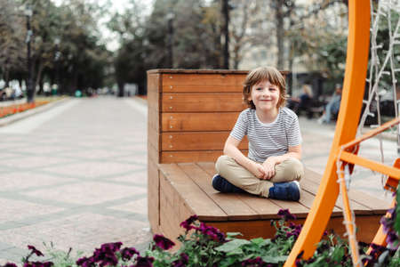 Smiling kid sitting on a wooden bench in the city park. Urban child boy weekend. Autumn outdoors leisure. Schoolboy free time outside