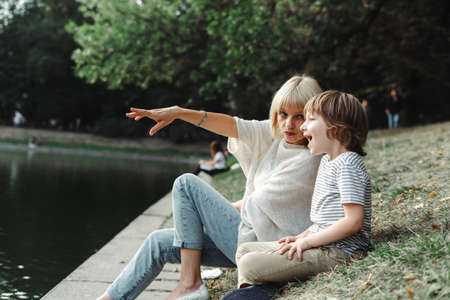 Mother and son sitting on the river bank in the park. Kid and his mom relaxing on pond shore in the grass. Woman points her hand on the lake. Family outside activities near water.