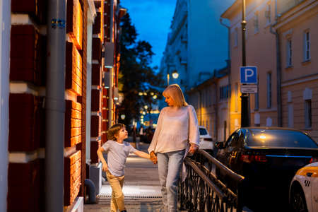 Mother and son walking in the city center street. Mom and kid taking a summer evening walk outside in the town. Family leisure time. City life. Banque d'images