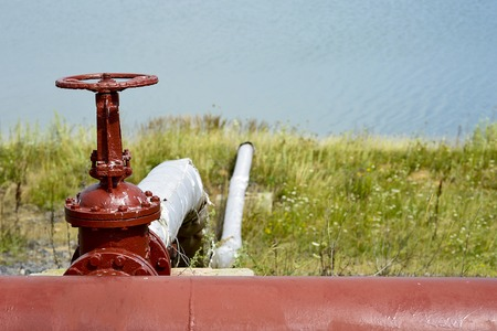 Shut-off valve of the pipeline against the background of an artificial lake