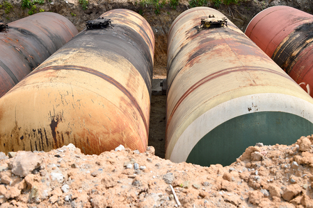 Large metal tanks are buried in the ground in the production warehouse. Stock Photo