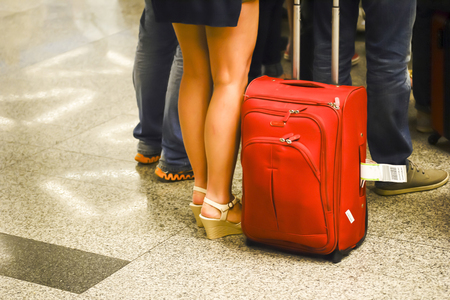 retractable: The womans legs with a large red suitcase on wheels in the foreground in anticipation of landing at the airport. Blurry. Stock Photo