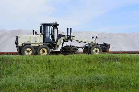 The grader is at the dam with pipeline in the background of mine. Side view. Foreground green grass.