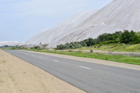 Asphalt road on the edge of the dumps of the mines of Belarus, the city of Soligorsk. Stock Photo