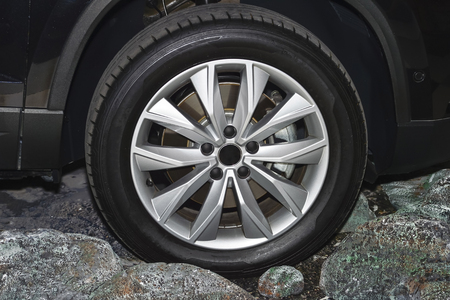 The front part of the black car, the wheel. Side view. Stock Photo