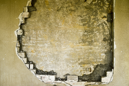 Partially destroyed wall inside an industrial building under demolition.