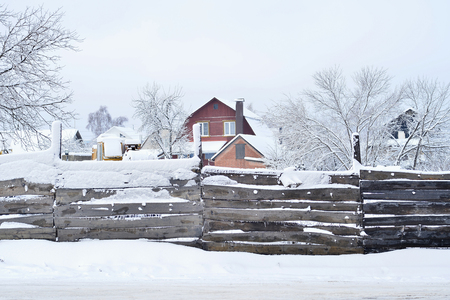 House with land and buildings, covered with snow, the view from behind the fence. Composition, background Banque d'images - 96398945
