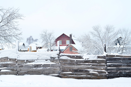 House with land and buildings, covered with snow, the view from behind the fence. Composition, background Banque d'images - 96398932