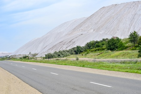 Asphalt road on the edge of the dumps of the mines of Belarus, the city of Soligorsk Stock Photo