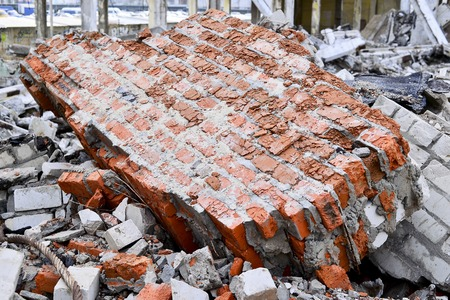 The remains of a concrete building. Part of the wall of red brick closeup lying in a pile of rubble Banco de Imagens