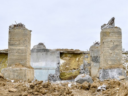The remains of the Foundation of a ruined large building. Hammered into the ground concrete piles sticking out of the ground up. Stock Photo