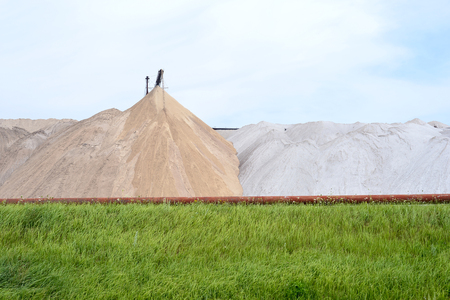 View of the salt mine and an artificial mound with green grass in the foreground. Stock Photo