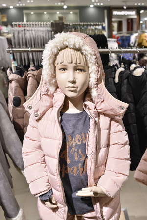 Mannequin girl child in a pink jacket with a hood in one of the shops at the Mall Gallery in Central Minsk, Belarus, February 2017.