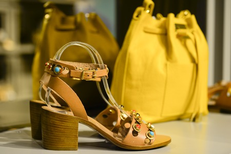 The composition in the window of a boutique: womens open toe shoes with a heel with a yellow bag in the background in a shopping center, Kings Avenue MALL, Paphos, Cyprus, June 2017.