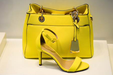 Yellow bag with a greenish tint in combination shoes the same colors. The concept of style and taste.