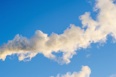 Smoke on blue sky background. Abstraction, a symbol