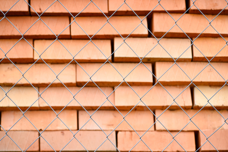Rows of red bricks ready for transport over the wire fence of the store. Background.