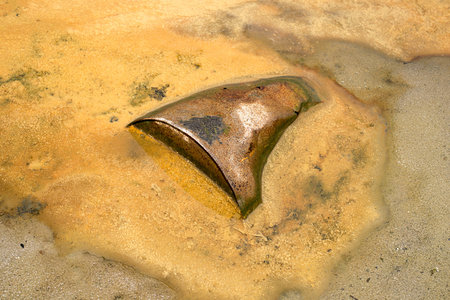 Rusty metal barrel sticking out of the sandy soil against the dirty yellow liquid.