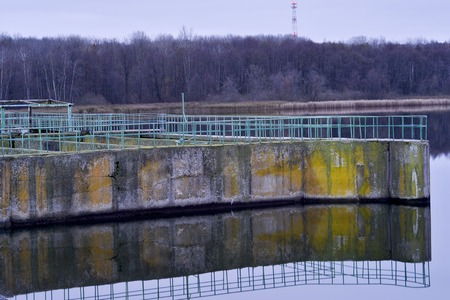 Part of a concrete structure of a dam on a large reservoir at dawn Фото со стока