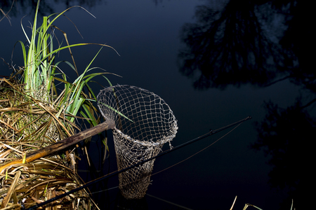 Vintage fishing net on the banks of the river at night. The symbol of fishing