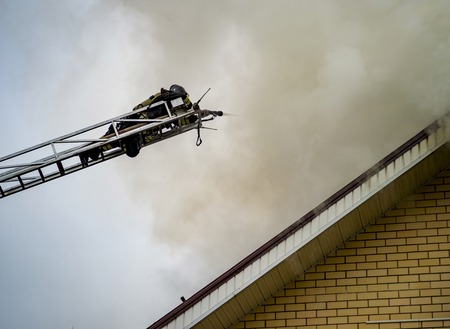 A firefighter puts out a burning building with height extension ladders. Stock Photo