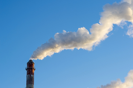 industrial smoke from chimney on blue sky. Stock Photo