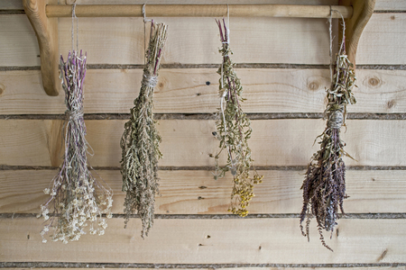 Dry bundles of medicinal plants hanging on the wall of the boards. Background, blurred. Banco de Imagens