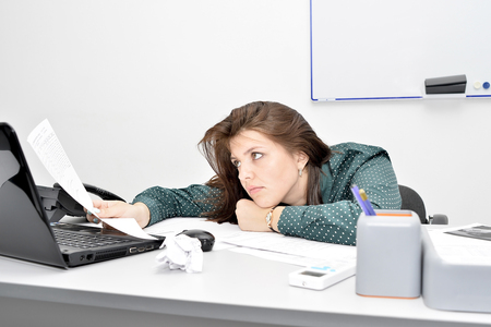 The brown-haired girl in the office at the laptop in a tired pose looks thoughtfully through the document.. Standard-Bild