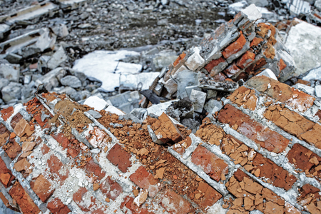 The remains of a concrete building. Part of the wall of red brick closeup lying in a pile of rubble.