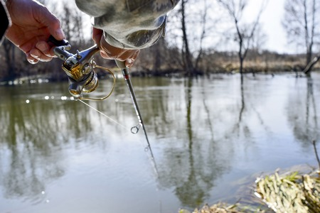 A fisherman catches a fish. Spinning reel closeup. Shallow depth of field on the spinning reel.