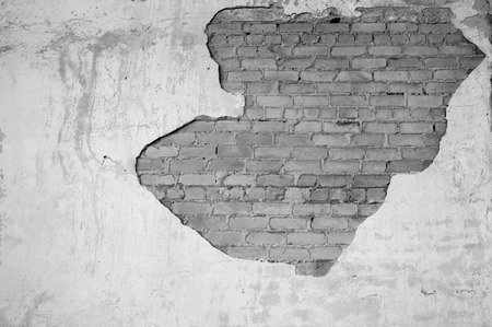 Wall with partially removed plaster in the form of figured drawing of a brick texture. Background. Black and white image.