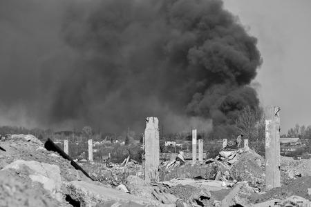 A pile of concrete rubble with protruding rebar on the background of thick black smoke in the sky. Black and white