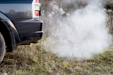 The back of the black car with the emission of smoke from the exhaust pipe on the background of nature. The concept of environmental pollution by vehicles.