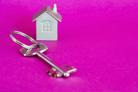 Metal key lock with imitation of the house in the form of a metal layout on a pink background with a purple hue. The concept of the offer of sale of real estate. Copy space.