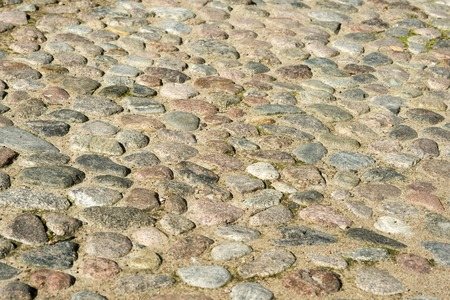 Cobblestone pavement of the ancient part of the city. Textured background.