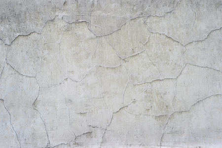 White concrete wall of the old house with curly cracks and swollen white paint. Background.