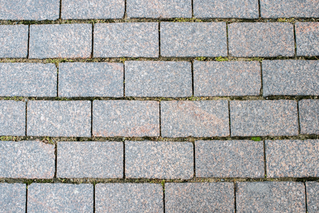 Granite pavement of the old part of the city. Background, texture. Shallow depth of field. view at an angle from above.