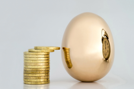 Shiny coins and a Golden egg which reflects the symbol of time and money. A broad concept of the relationship of time and money, business success, conventions and relativity of things. 写真素材